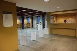 Y63-E, Bibliothek: Rechts der Info-Schalter E-04A, links der Eingang zur Bibliothek mit Kontrollschranken in den Raum E-03. Im Hintergrund ist die Selbstausleihe-Station zu erkennen.