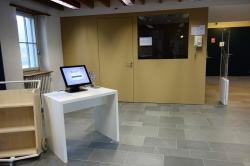 Y63-E, Bibliothek: Die Selbstausleih-Station im Raum E-03. Im Hintergrund ist der Auskunft-Schalter E-04A mit dem internen Telefon zu sehen.